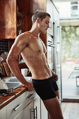 Buy stock photo Shot of a muscular young man standing in the kitchen wearing only underwear while contemplating at home
