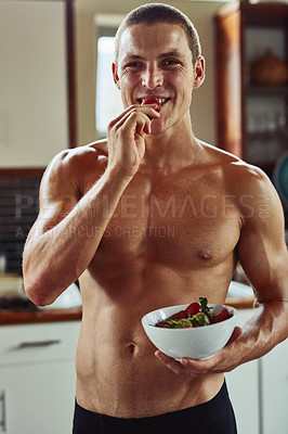 Buy stock photo Portrait of a cheerful young man  wearing only his underwear while enjoying a bowl of strawberries in the kitchen at home