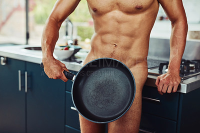 Buy stock photo Shot of an unrecognizable naked man holding a frying pan in front of his private area in the kitchen at home