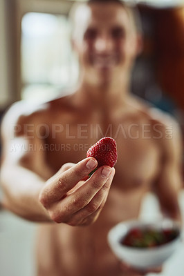 Buy stock photo Closeup of a cheerful young shirtless man holding out a strawberry at the camera at home during the day