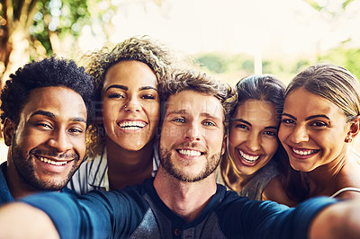 Buy stock photo Portrait of a group of friends taking a selfie together outdoors