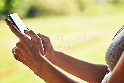 Buy stock photo Closeup shot of an unrecognizable woman using a cellphone outdoors