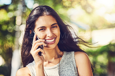 Buy stock photo Portrait of an attractive young woman talking on a cellphone outdoors