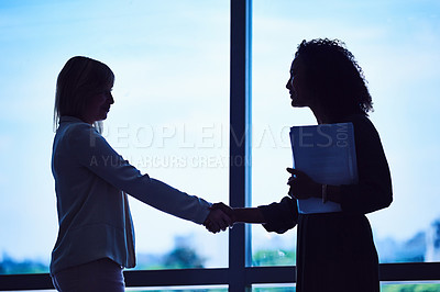 Buy stock photo Silhouette of two unrecognizable businesswomen shaking hands in the office