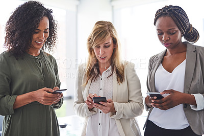 Buy stock photo Cropped shot of a group of businesswomen using cellphones in the office