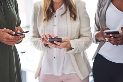 Buy stock photo Cropped shot of a group of unrecognizable businesswomen using cellphones in the office