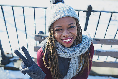 Buy stock photo Shot of a beautiful young woman making a peace gesture on a snowy day outdoors