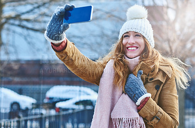 Buy stock photo Shot of an attractive young woman taking a selfie in the snow outside