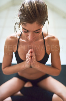 Buy stock photo Cropped shot of an attractive young female athlete meditating at home