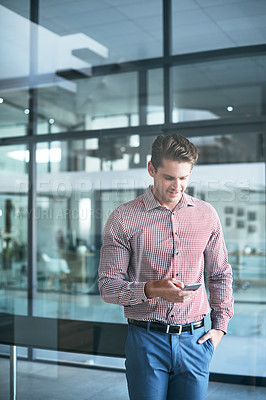 Buy stock photo Shot of a young businessman using a cellphone in an office