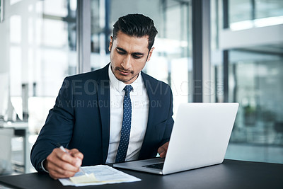 Buy stock photo Shot of a young businessman writing notes while working on a laptop in an office