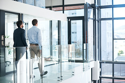 Buy stock photo Rearview shot of two businessmen walking in a modern office