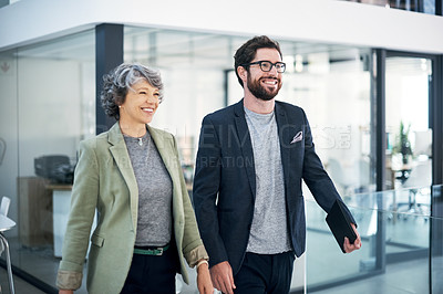 Buy stock photo Shot of two businesspeople walking in an office