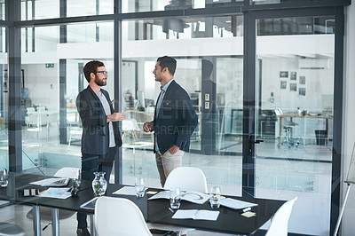 Buy stock photo Shot of two young businessmen having a meeting in a modern office