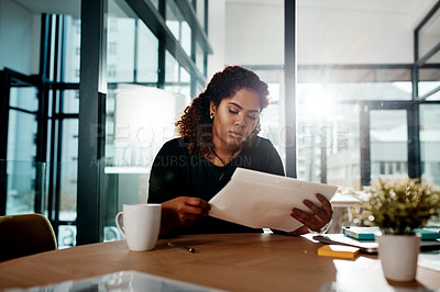 Buy stock photo Shot of a young businesswoman going through some paperwork in an office