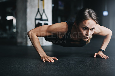 Buy stock photo Shot of an attractive young woman doing push ups in a gym