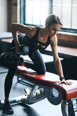 Buy stock photo Shot of a young woman working out with weights in a gym
