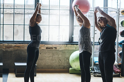 Buy stock photo Shot of mature women stretching with a young female instructor during a training class at the gym