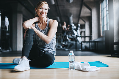 Buy stock photo Full length portrait of an attractive young woman listening to music while working out in the gym