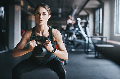 Buy stock photo Cropped shot of an attractive young woman working out with a kettle bell in the gym