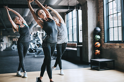 Buy stock photo Full length shot of three attractive and athletic women stretching before their workout in the gym