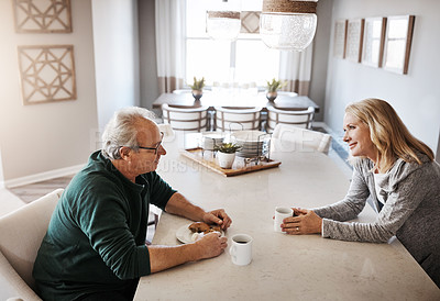 Buy stock photo Shot of a mature couple having coffee and a snack during a relaxed day at home
