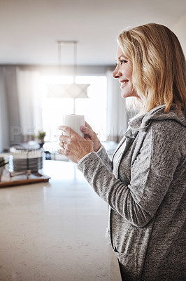 Buy stock photo Shot of a mature woman relaxing at home with a cup of coffee
