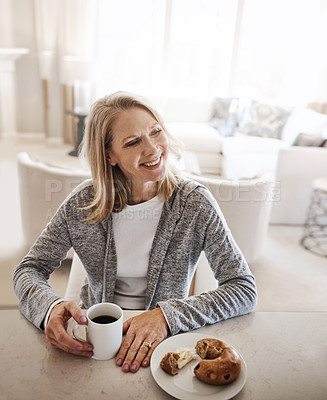 Buy stock photo Shot of a mature woman having coffee and a snack during a relaxed day at home
