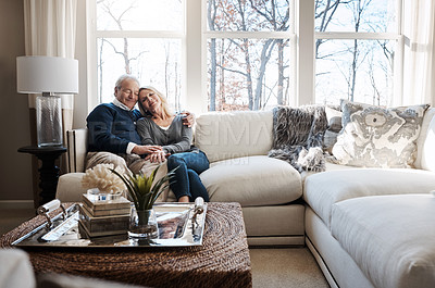 Buy stock photo Shot of a loving mature couple relaxing together at home