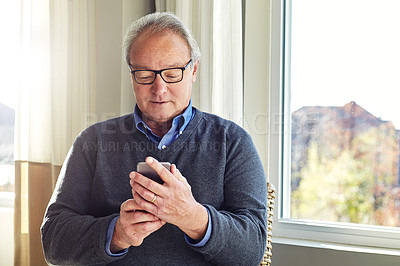Buy stock photo Cropped shot of a senior man using a cellphone at home