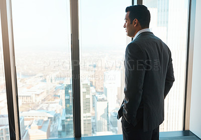 Buy stock photo Shot of a young businessman looking out the window in an office