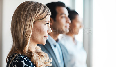 Buy stock photo Shot of a young businesswoman standing in an office with her colleagues in the background