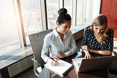 Buy stock photo Shot of two businesswomen working together on a laptop in an office