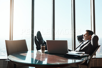 Buy stock photo Shot of a young businessman relaxing with his feet up on a table in an office