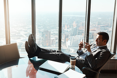 Buy stock photo Shot of a young businessman using a cellphone while relaxing with his feet up on a table in an office