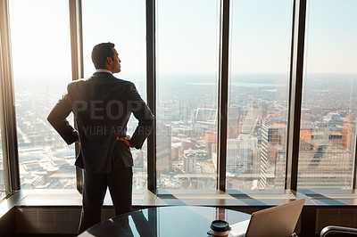 Buy stock photo Rearview shot of a young businessman looking out the window in an office