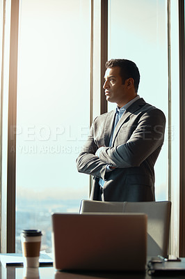 Buy stock photo Cropped shot of a handsome young businessman standing with his arms folded in the office