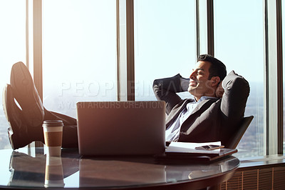 Buy stock photo Cropped shot of a handsome young businessman looking relaxed while sitting in his office