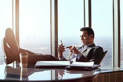 Buy stock photo Cropped shot of a handsome young businessman reading a text message while sitting in his office