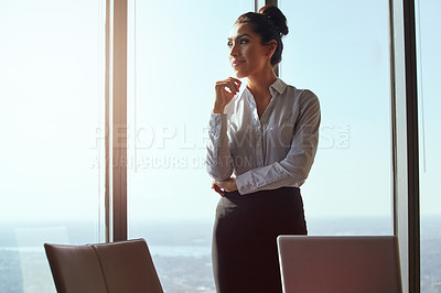 Buy stock photo Cropped shot of an attractive young businesswoman looking thoughtful while standing in her office