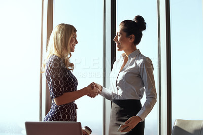 Buy stock photo Cropped shot of two young businesswoman shaking hands in their office
