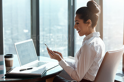 Buy stock photo Cropped shot of an attractive young businesswoman reading a text message while working in her office