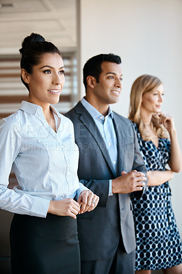 Buy stock photo Cropped shot of three young businesspeople standing in their office