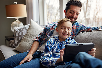 Buy stock photo Shot of a little boy using a digital tablet with his father at home