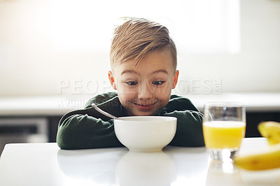 Buy stock photo Cropped shot of an adorable little boy having breakfast while sitting in the kitchen