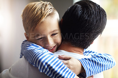Buy stock photo Shot of an adorable little boy hugging his father at home