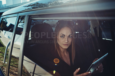 Buy stock photo Shot of a young businesswoman using a digital tablet while traveling in a car
