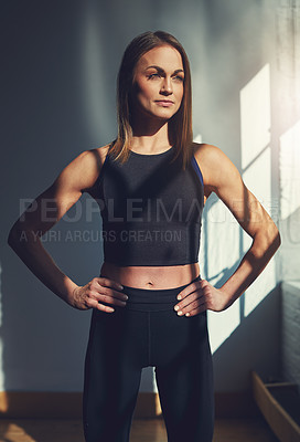 Buy stock photo Cropped shot of an attractive young sportswoman looking thoughtful while standing with her hands on her hips