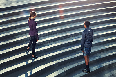 Buy stock photo High angle shot of two young sportspeople standing on stairs during their outdoor workout