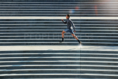 Buy stock photo Full length shot of a handsome young sportsman running up and down stairs outside